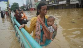 Seorang ibu yang sedang menggendong anaknya berjalan melewati genangan air.