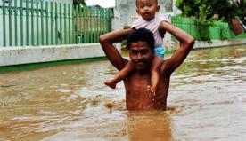 Seorang bapak memangku anaknya ditengah kondisi banjir. Terlihat banjir mencapai ketinggian perut dari orang dewasa.